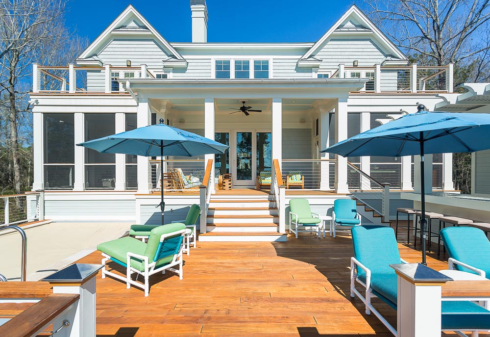 The rear of the house features a sprawling natural wood deck, holding a pool at left, plus an array of brightly colored blue and green furniture. Overhead, a pair of bedroom access balconies overlook the space.