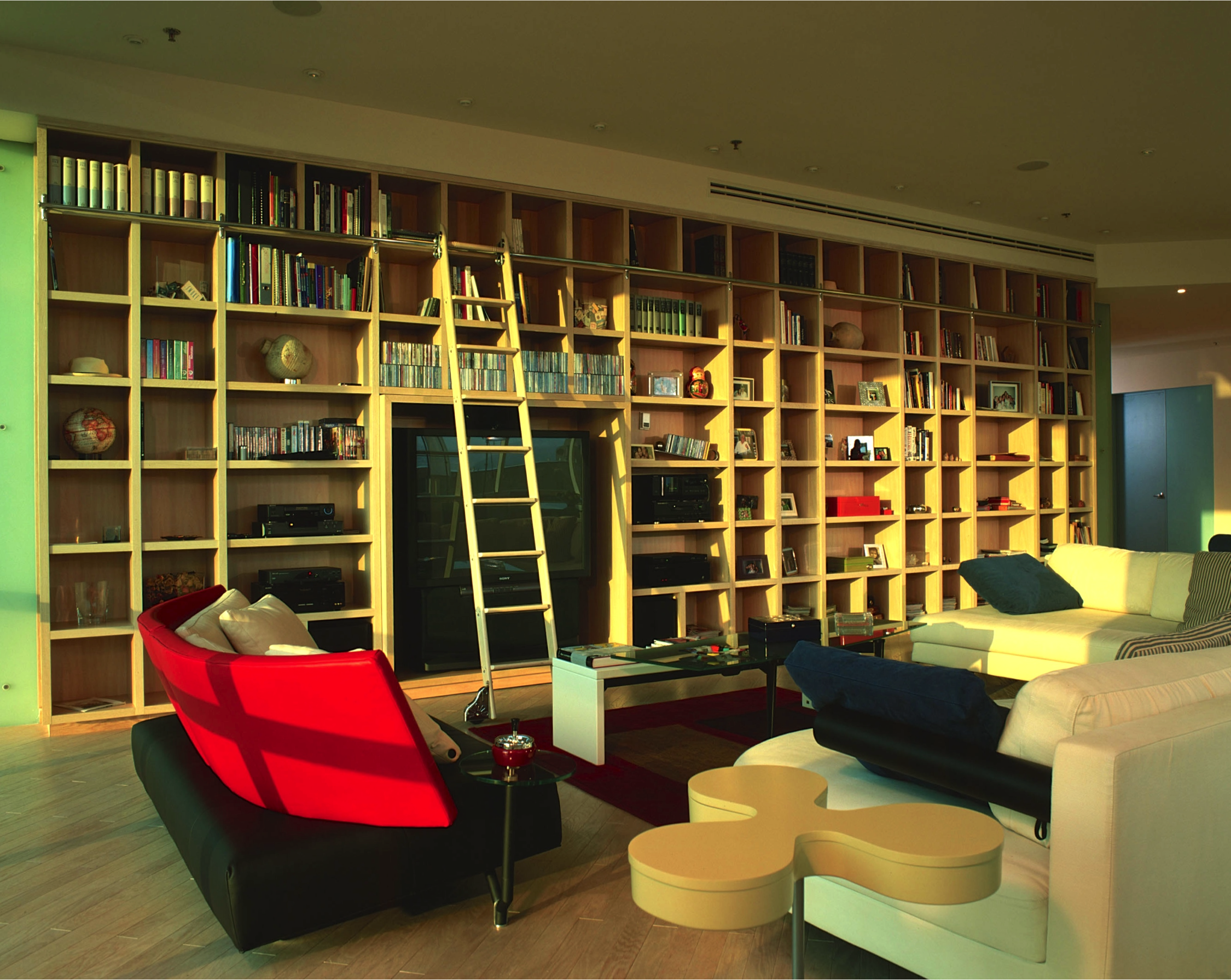 A sunset view of the living room. The entertainment center is tucked neatly into the rest of the bookcase. Recessed lighting above the bookcase wall keeps the room bright after the sun sets.