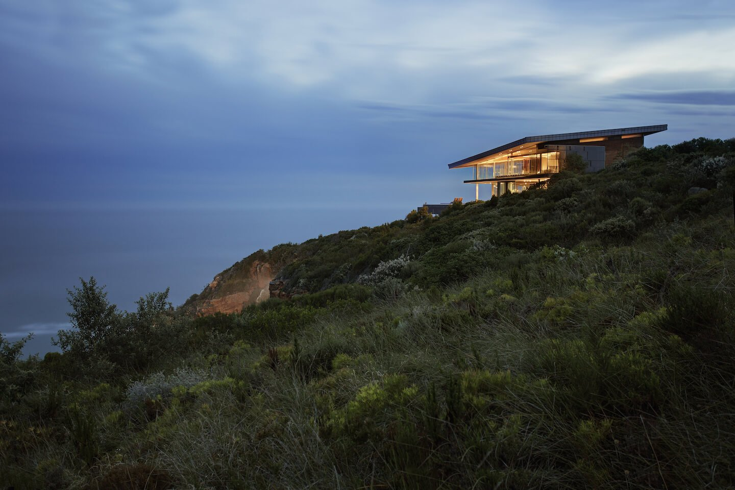 Profile view of the landscape highlights the blended-in nature of the structure, with a roof slant paralleling the slope. Floor to ceiling glass allows for spectacular ocean views.