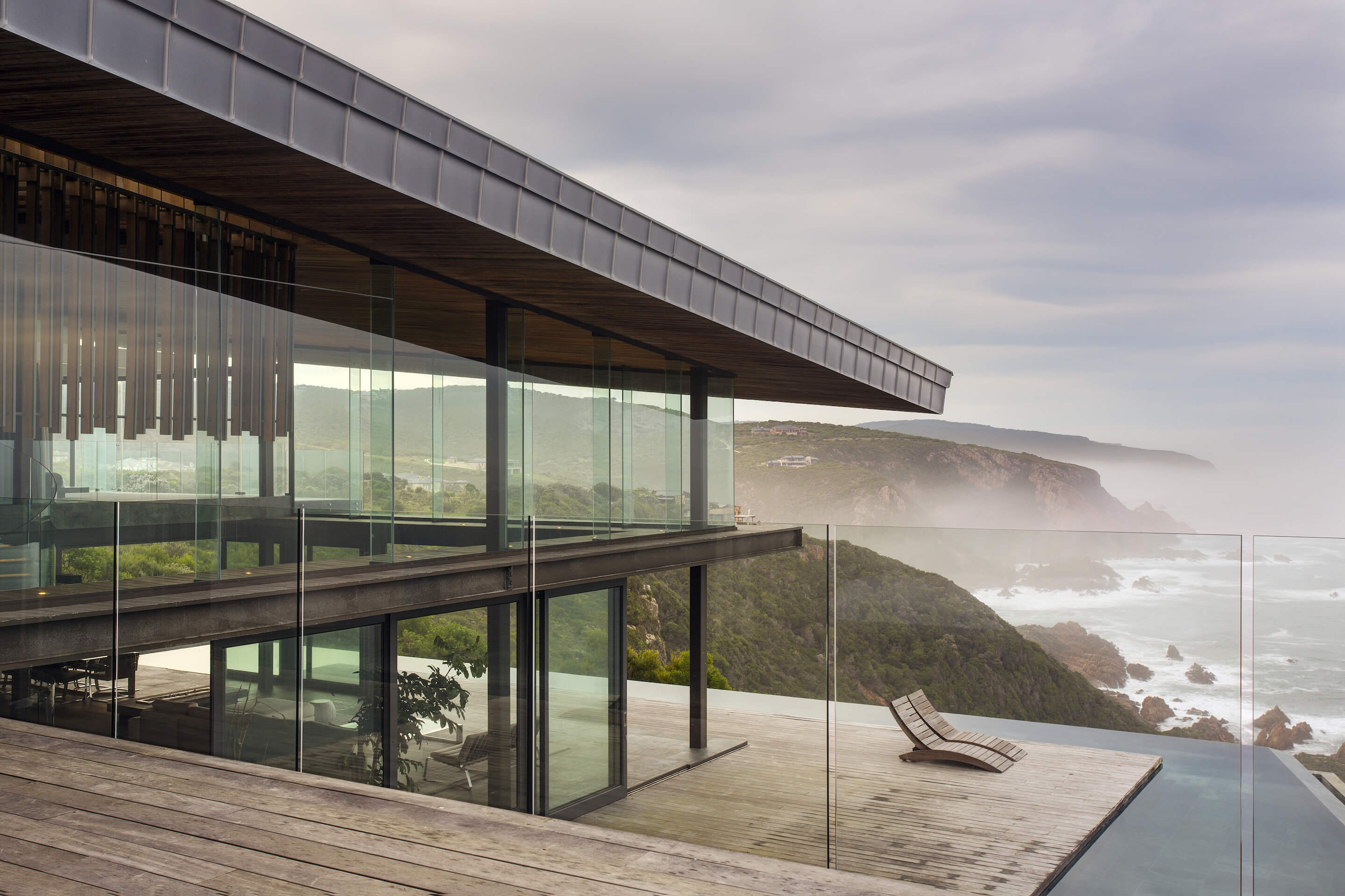 Glancing through the frameless glass panels surrounding the upper balcony, we see the large expanse of timber patio, open design two story living room, and surrounding lido pool with expansive views of the cliffs and ocean.