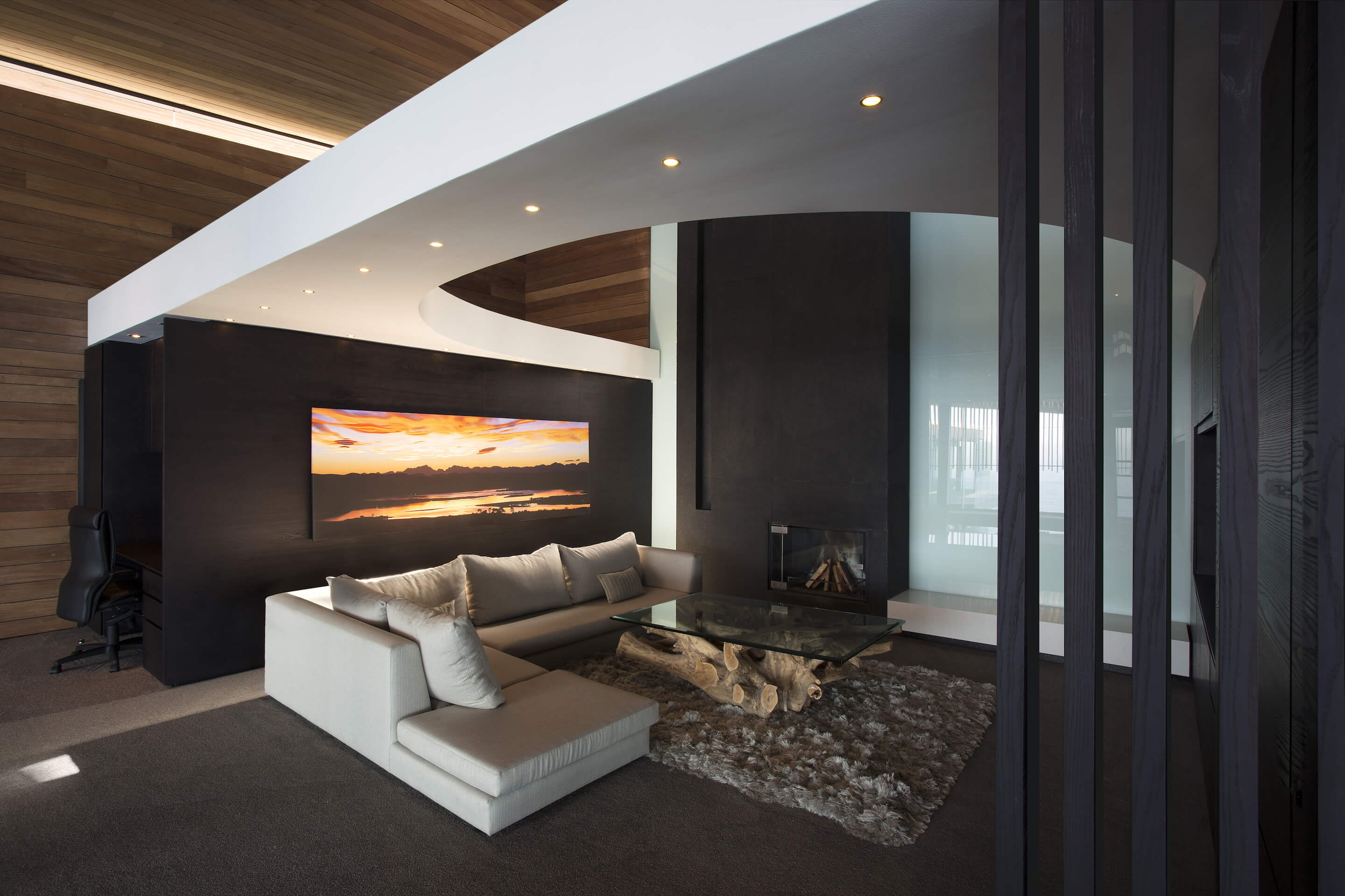 At the center of the upstairs area, we see this cozy space standing below a circular cut white ceiling piece, surrounded by dark stained wood. Small fireplace built into far wall is complemented by large sunset artwork and log-style, glass-topped coffee table.