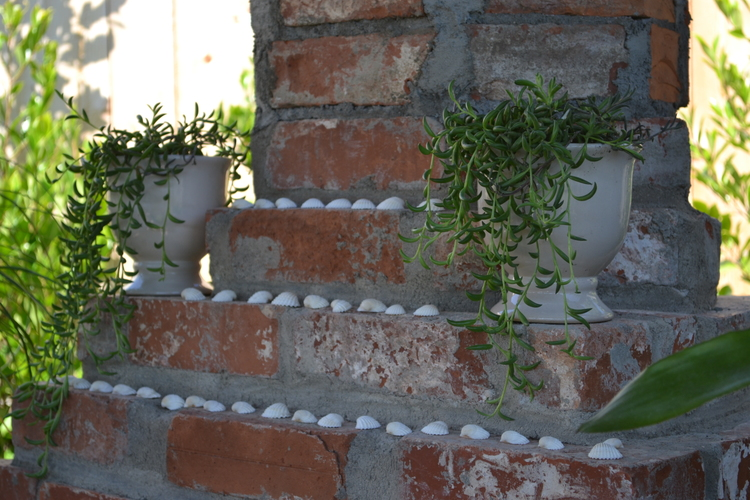 A multi-tiered brick and mortar sculpture with plenty of room for planters. Small shells lined up along the tiers add a beachy feel.