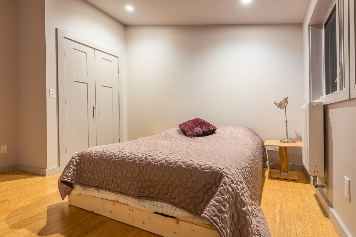 This simple bedroom continues the hardwood floor of the lower level and the industrial design in the lamp and night stand. A large closet rounds out the room.