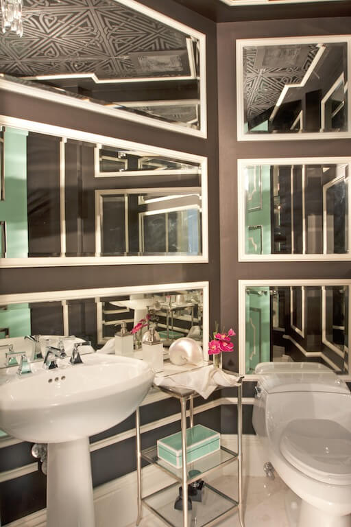 This brown and Tiffany blue half bathroom is heavily mirrored and has a wallpapered ceiling.