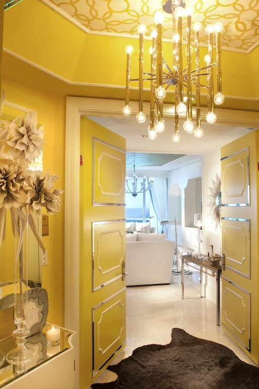 The yellow foyer opens into a white living room. Metal wainscoting on the door really brings in the glamor. The wallpapered ceiling makes another appearance here, this time in yellow.