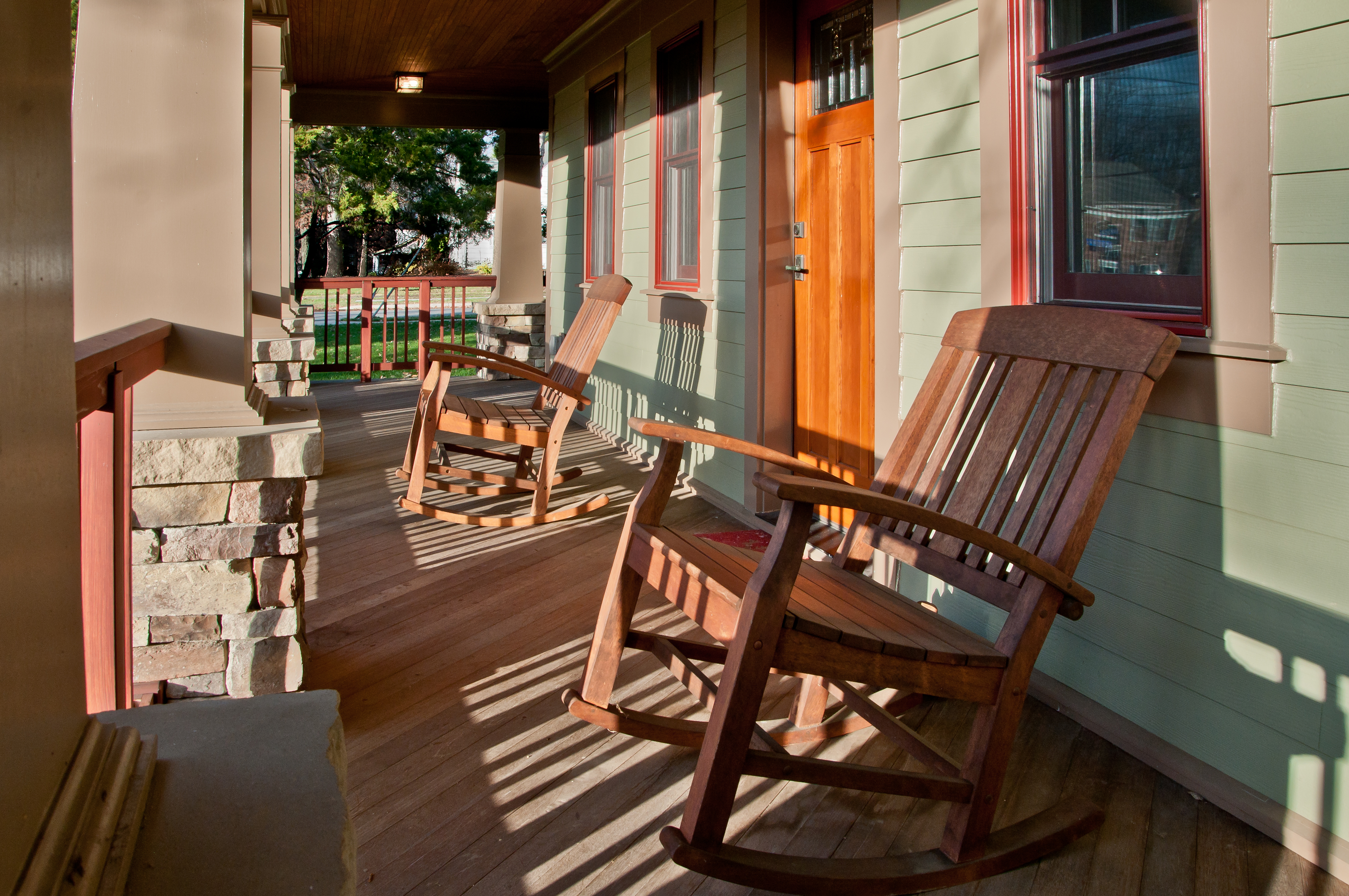The stone and wood front porch has two rocking chairs flanking the door. The mint-green exterior contrasts with the warm, bright wood front door.