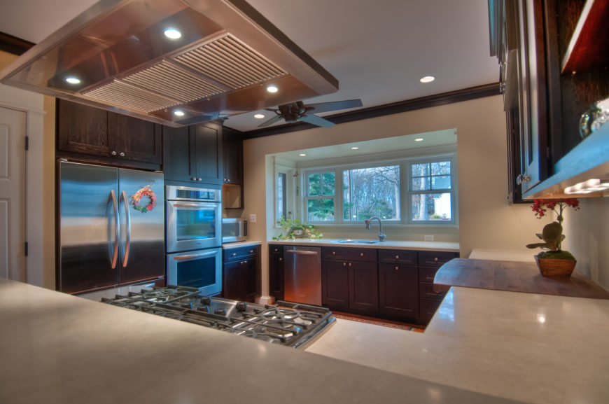 The contemporary kitchen is furnished with stainless steel appliances, white granite countertops, and rich dark wood cabinets. The smooth white countertops are interrupted only by a wooden butcher's block on the right side.