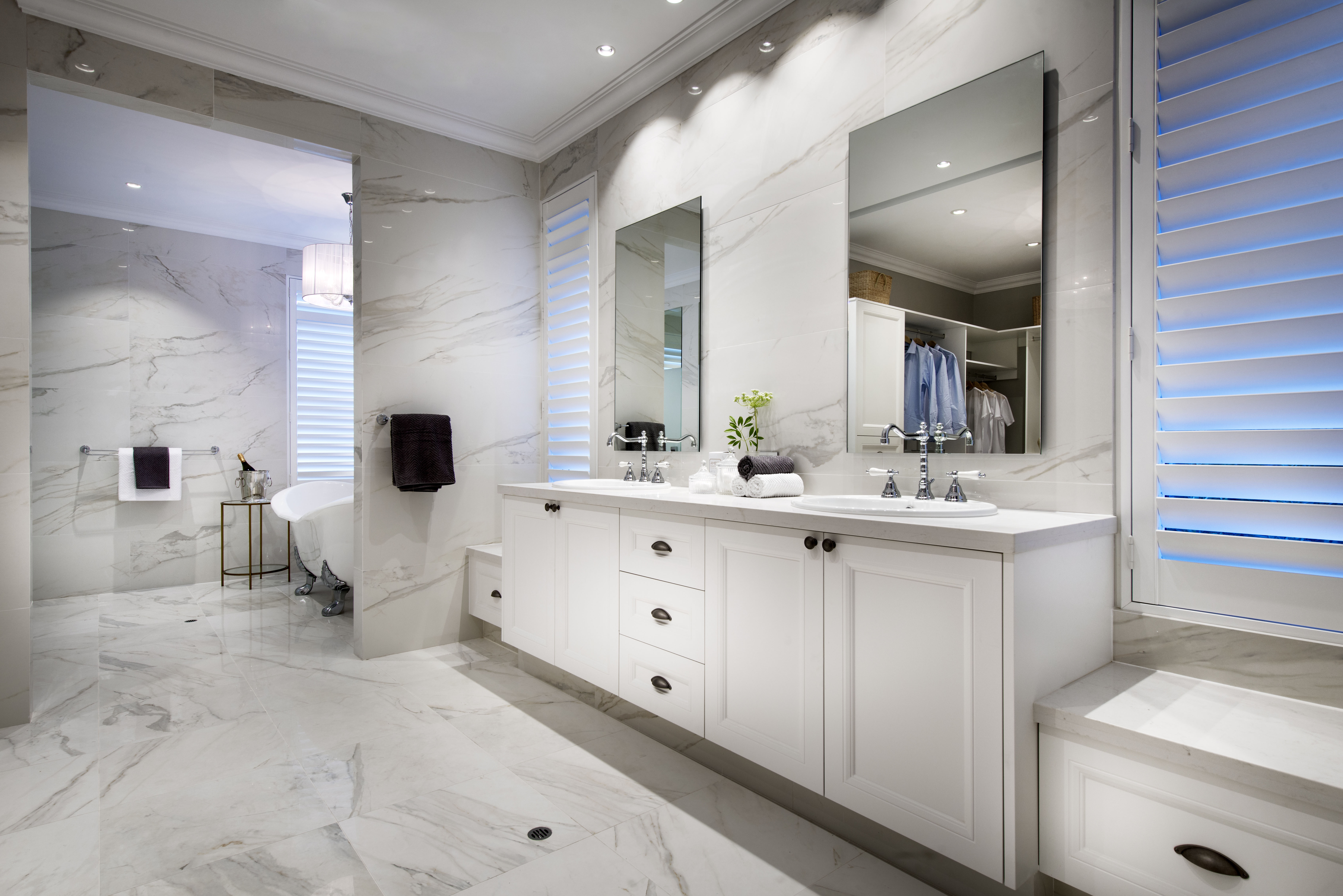 Off the primary bedroom is the enormous primary bathroom, separated into three sections. Shown here is the vanity with his-and-hers sinks, dual laundry baskets, and the separate room with a claw-foot bathtub.