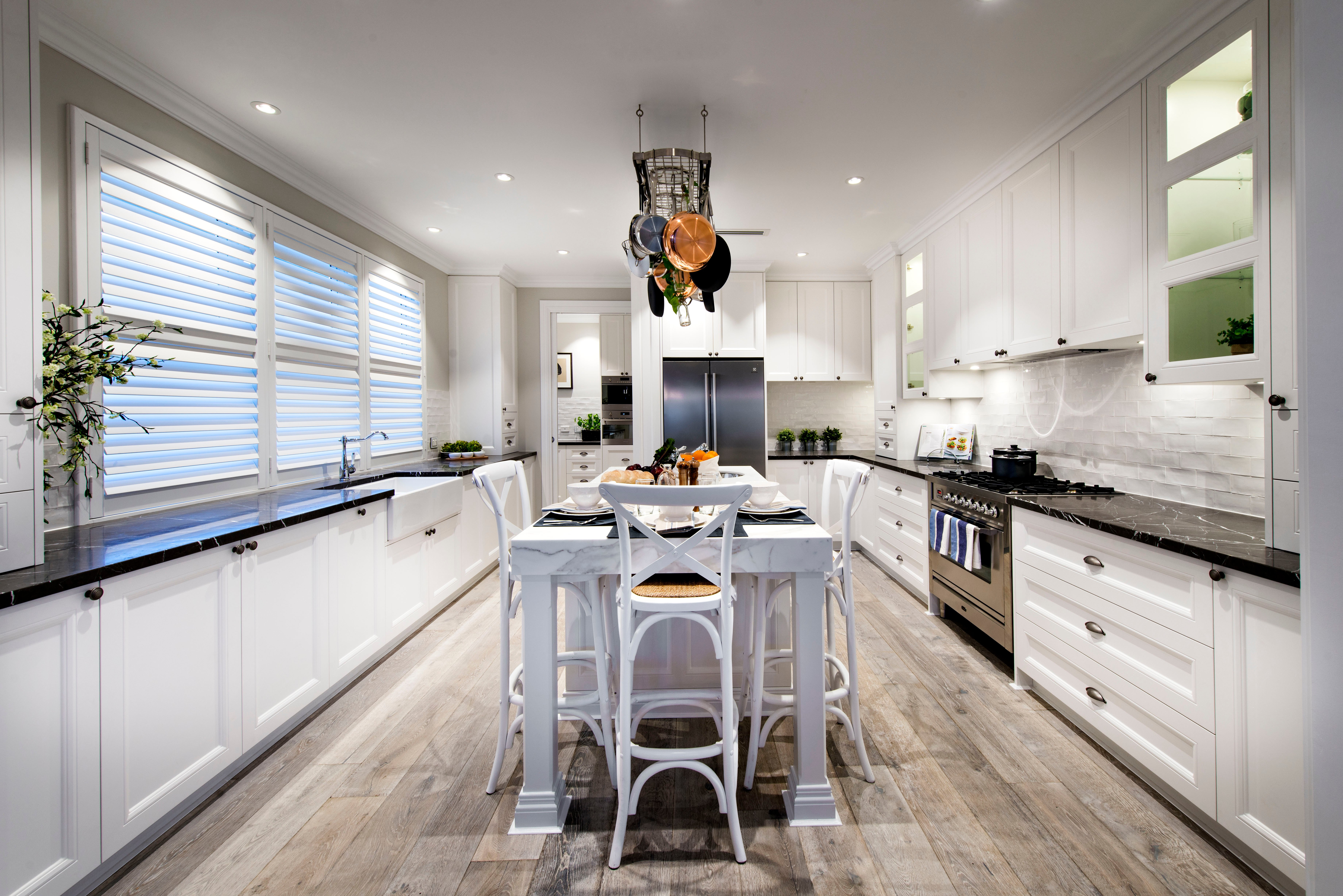From inside the doorway, it's easier to see the sheer size of the kitchen. Large cabinets and drawers line the walls, and wall-cabinets provide even more storage space. Through the doorway beyond, the kitchen continues with a double convection oven and even more cabinets.