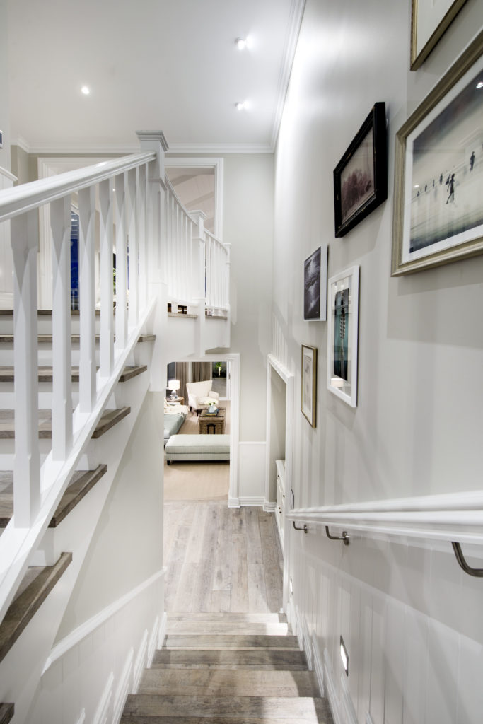 While descending the staircase, small lights can be seen. Beyond the stairs is the family room.