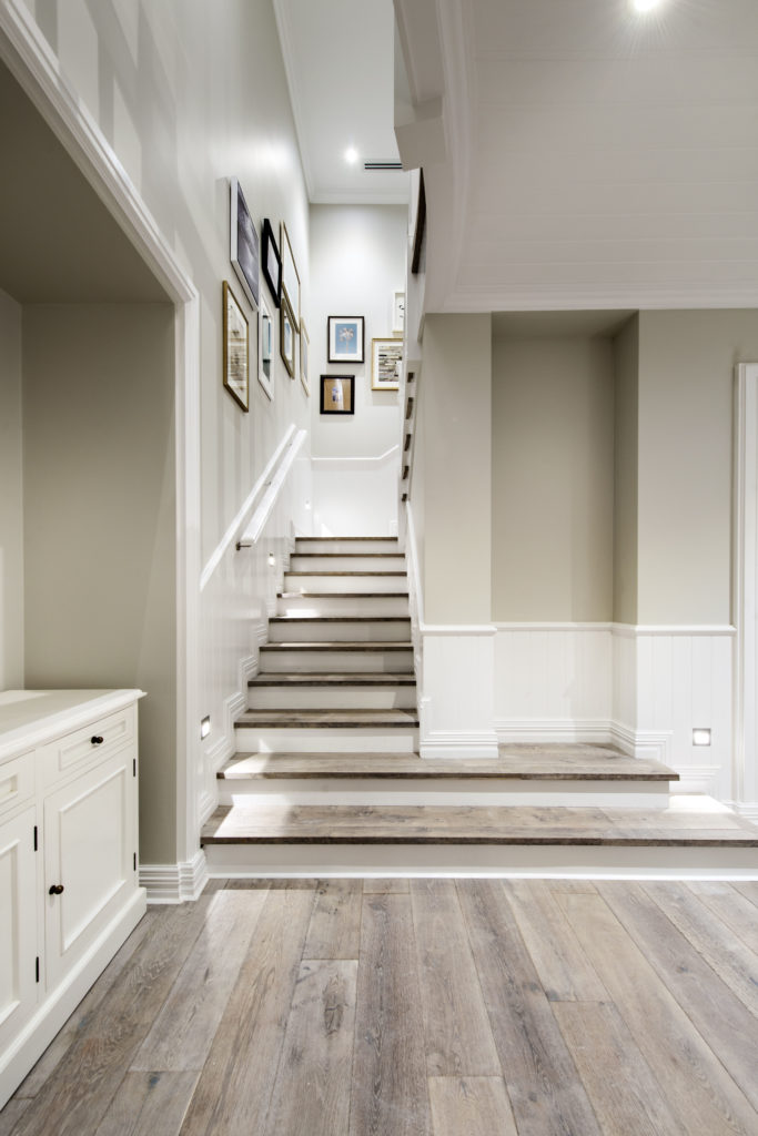 At the foot of the narrow two-flight staircase lined by more wainscoting and a slim white handrail, we see a series of photographs decorating the walls.