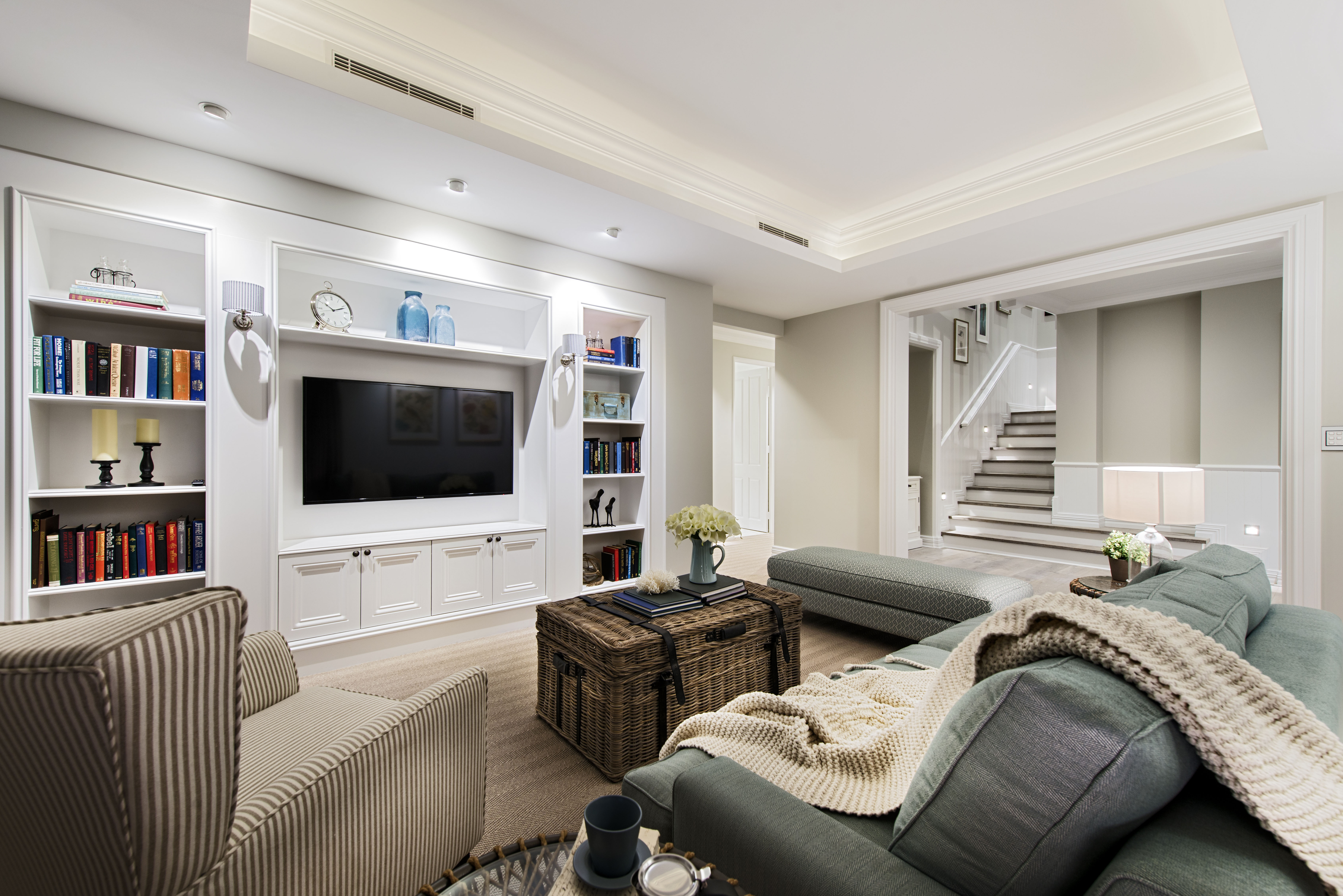 The family room has lots of comfortable, cozy seating, a large home theater, and built-in shelving and bookcases surrounding the media center.