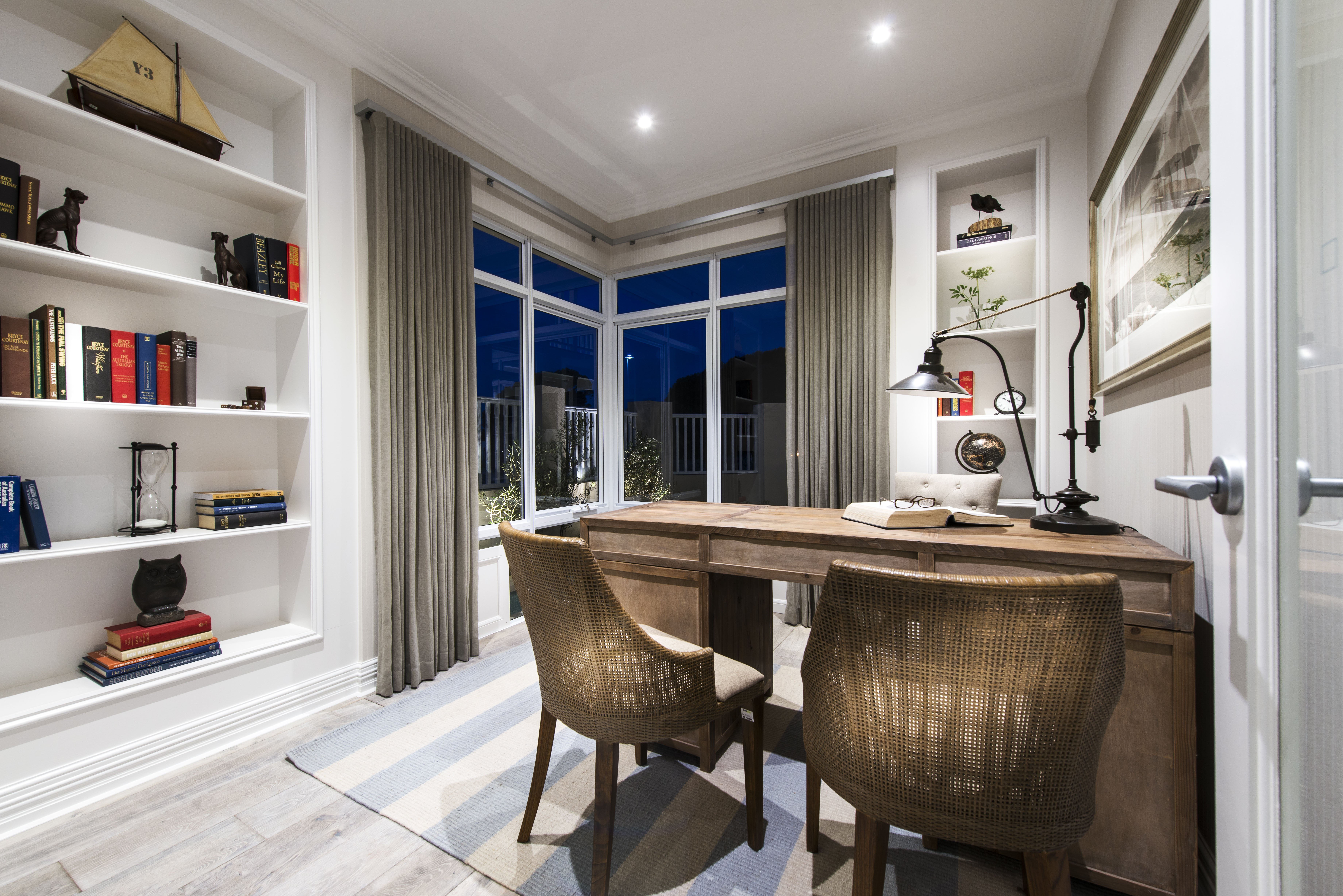 The home office has large built-in bookcases and a striped area rug beneath the desk. Large windows in the corner provide natural light.
