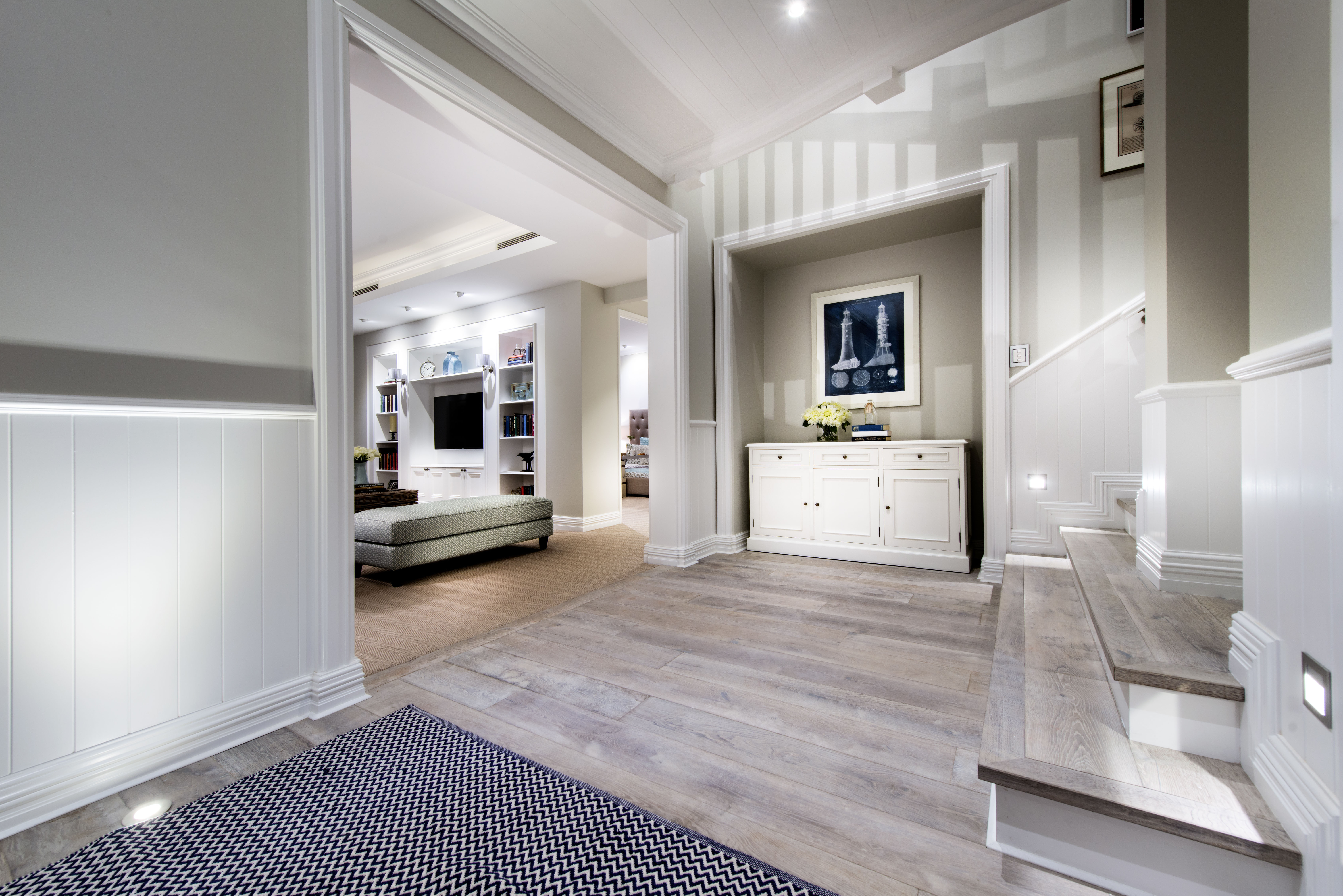 imple rug marks the entryway to the home. Set into a former closet is a white buffet for storage. To the right, stairs lead up to the second floor and the main living area. To the left, the family room is visible. The walls are light olive with white wainscoting.