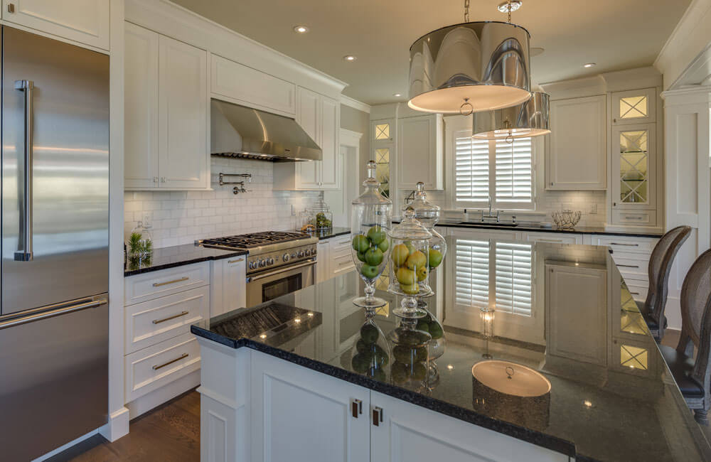 A close-up view of the eat-in kitchen with an enormous granite island. Stainless steel appliances are complemented by the pendant lighting above the island.