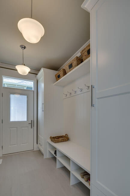 An all-white mudroom with plenty of storage options; lockers, hooks, and above-and-beneath the bench shelving.