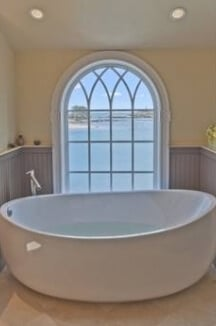 A close up of the bathtub displaying the amazing view outside of the window.