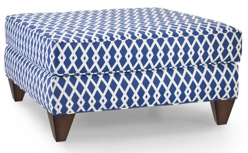 Patterned blue and white ottoman with exposed wood legs.