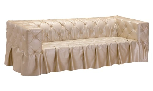 This is a daringly comfortable and stylish sofa in a rich gold faux leather upholstery that is covered in button tufting. The seamless skirt, which is just an extension of the upholstery, gives this piece an extra elegant polish.