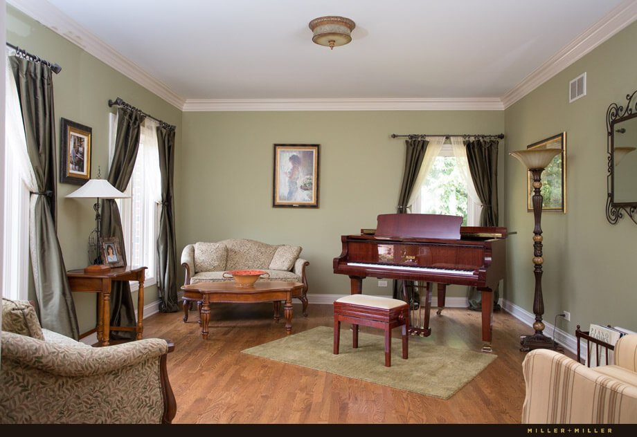 A small music room with a rich cherry piano and several traditional style armchairs and sofas comes off from the entryway.