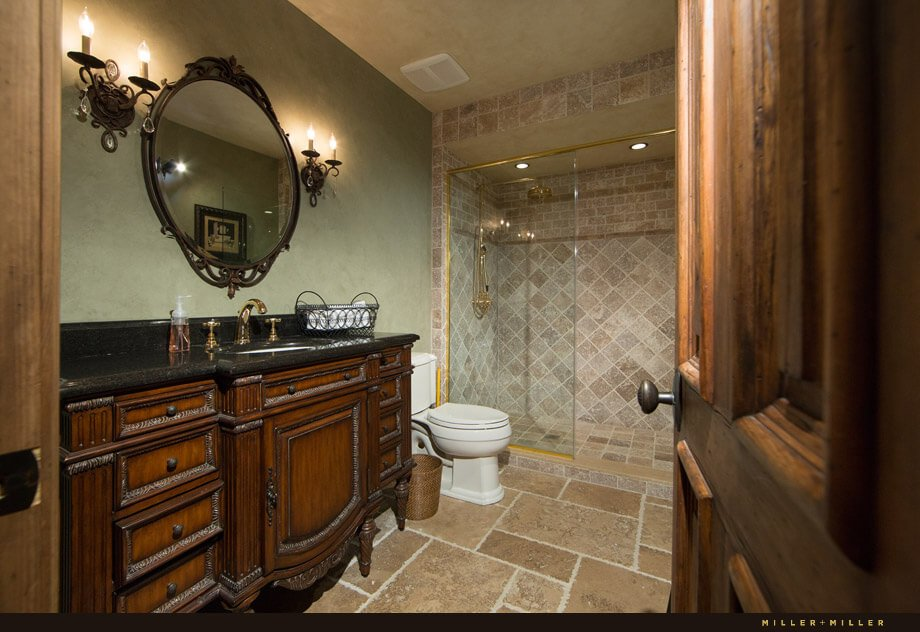 The third bathroom has an antique vanity with a black marble countertop. A glass-enclosed tile shower takes up the back section of the room.