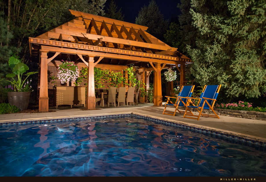 The large pool takes up the majority of the backyard. In the back right corner is another wooden shelter with an additional dining area. The back of the shelter is covered in grape vines.