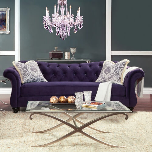This bold royal purple sofa has a sleek, elegant silhouette that features a solid wood frame with scroll armrests, a sweetheart backrest and glossy black turned-bun feet. The backrest is adorned with crystalline acrylic button tufts that add a bit of glitz and glitter to this elegant piece.