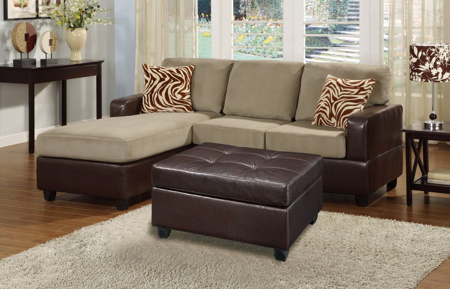 This contemporary three-piece sectional sofa has plush reversible microfiber cushions in a beige/gray color and comes with two zebra accent pillows and a faux leather cocktail ottoman. The chaise can be switched from the left to the right side.