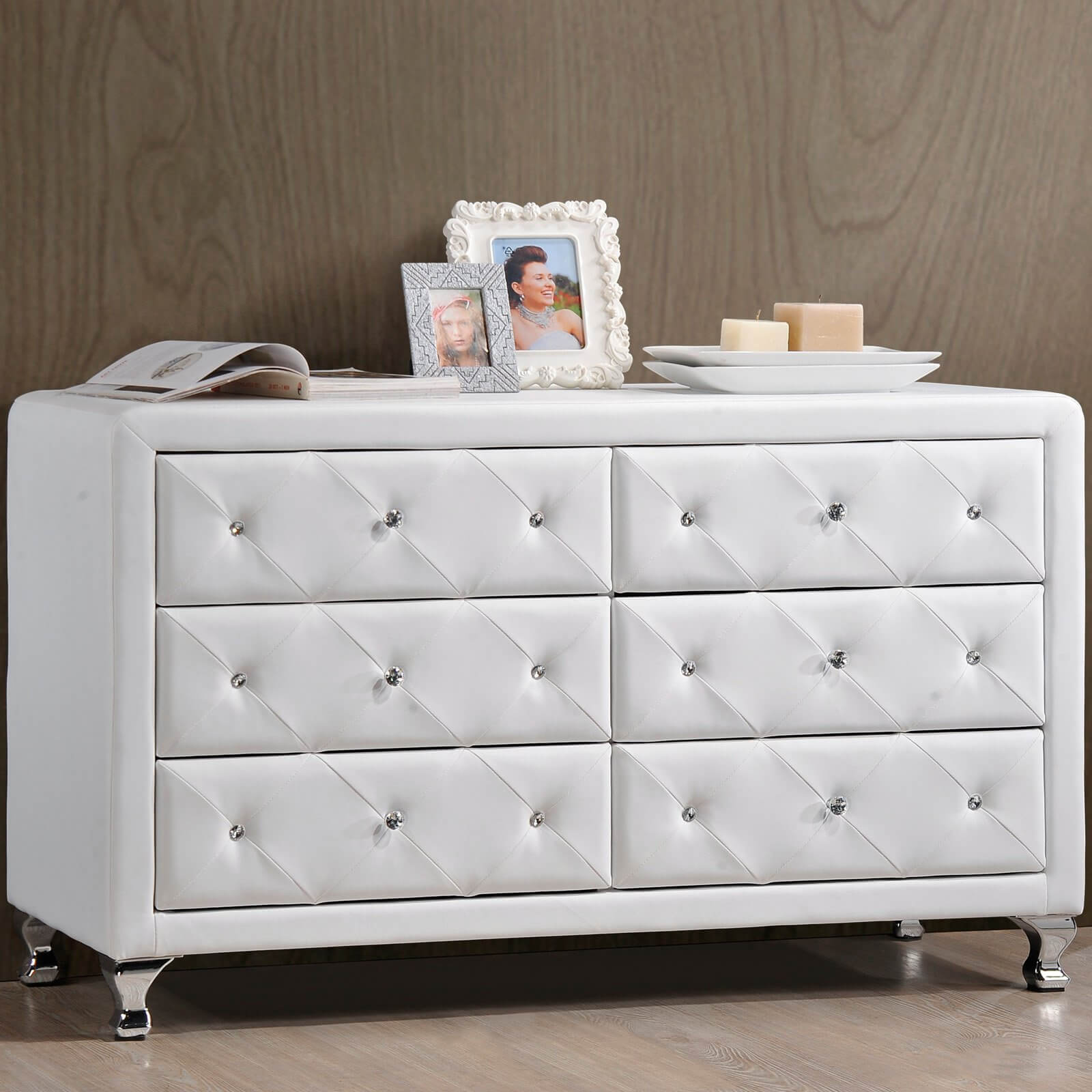 While the framework of the dresser itself is built from wood, some pieces boast a fully leather surface, for a rich, textural look. This example features button tufted drawers in white leather upholstery.