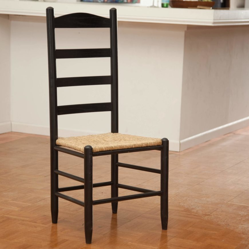 """Shaker style is a very specific strain of utilitarian, minimalist design. These chairs, equipped with a """"ladder back,"""" are designed to be hung up when not in use. Our example shows off the flat angles and unfussy touches common in this style."""