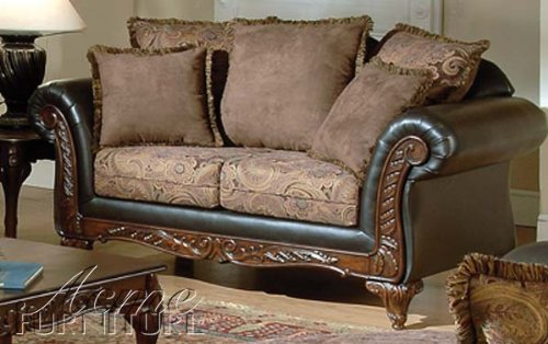 This majestic and elegant sofa combines a subtle floral pattern with sleek expresso leather and a rich dark hardwood frame. The frame features hand-carved leaf scroll carvings in the French Provincial style.