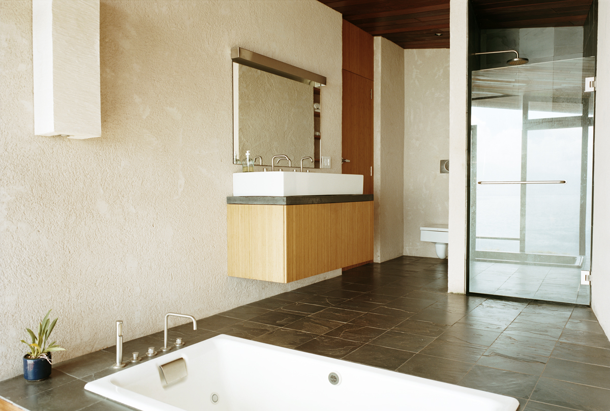 This bathroom features a floating wood vanity with extra wide double-tap sink, dark stone floor tiles and a lowered soaking tub. Glass enclosure shower stands at right.