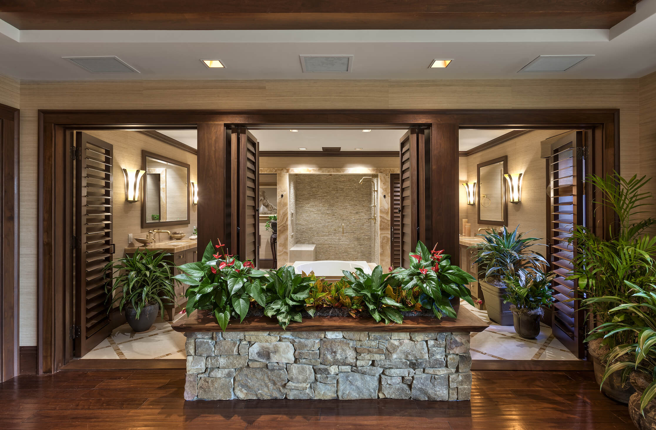 This area is the entrance to one of the vast bathrooms. A stone wrapped planter feature stands before a trio of louvered wooden doors, giving way to the bathroom itself.