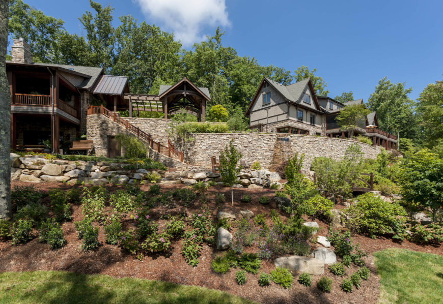 The entire estate is wrapped in immaculate landscaping, utilizing large stone pieces and the natural topography to striking effect. Water features can be seen running down the upper garden wall at center.