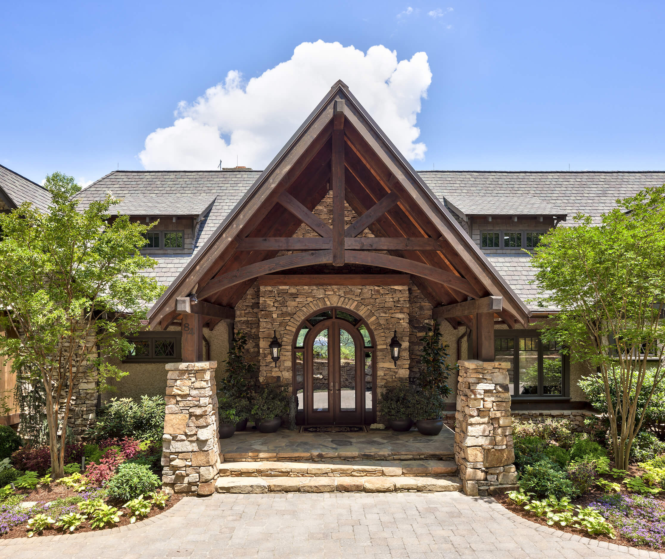 The grand entrance makes use of stone and natural wood exposed beams for a bold, rustic greeting to those entering the home. From the drive, the interior is made private via obscured windows and shading.