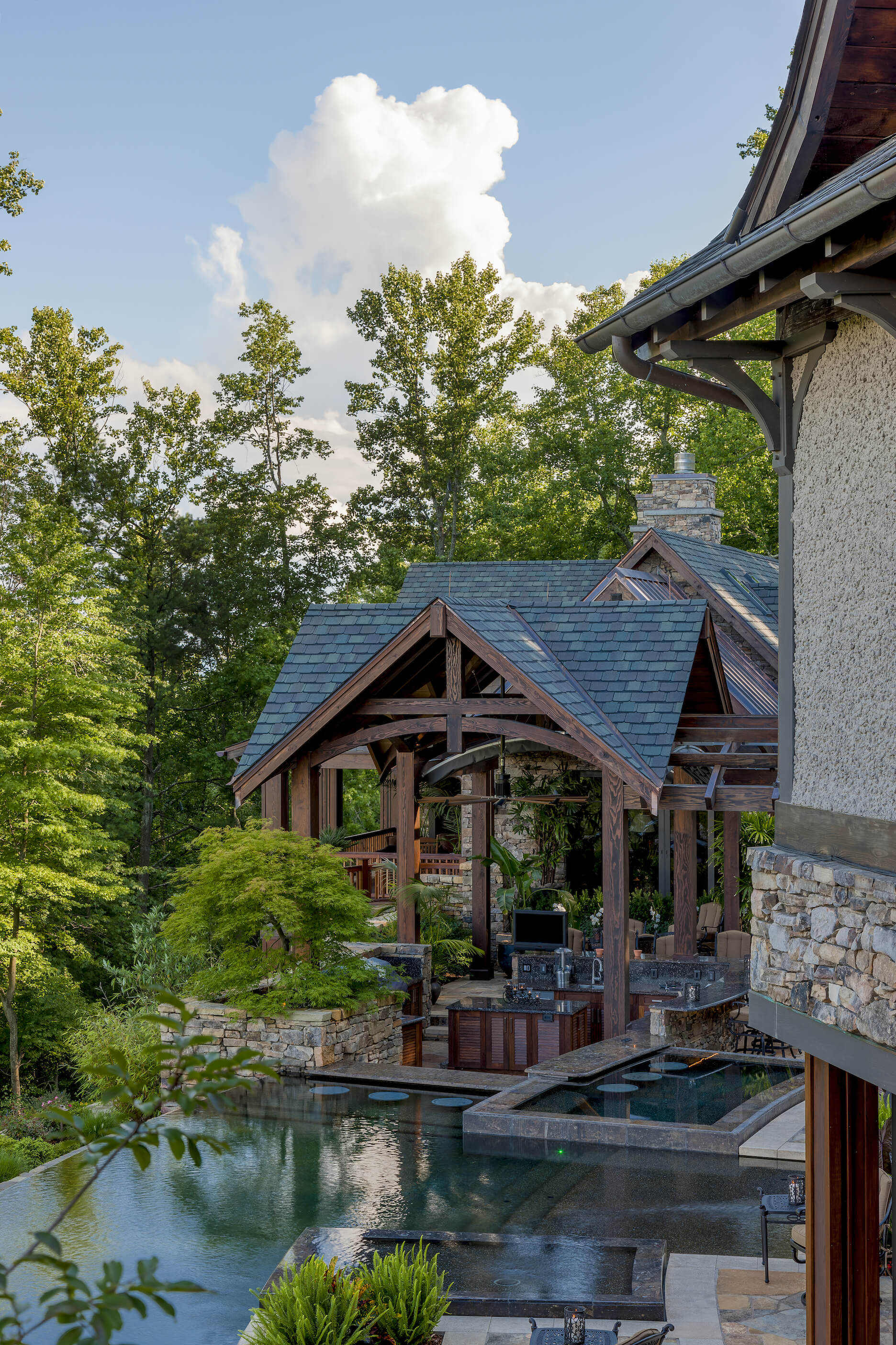 Here he have the fully featured outdoor summer kitchen, with rich wood cabinetry and granite countertops, beneath a shelter structure. Water features abound, including the infinite edge pool seen at left.
