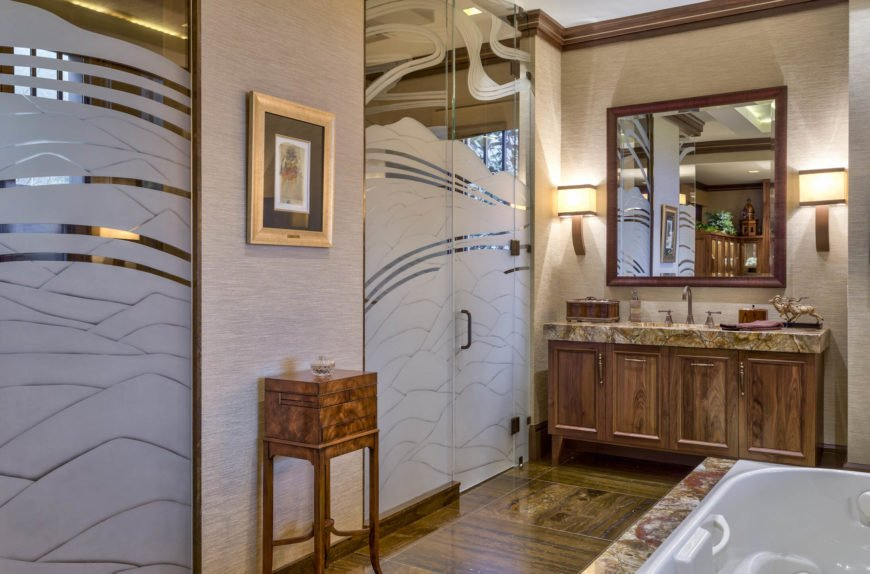 Mirrored glass shower stalls with etched artwork stand across from the soaking tub. Contemporary cubic sconces flank the mirrors in this bathroom.