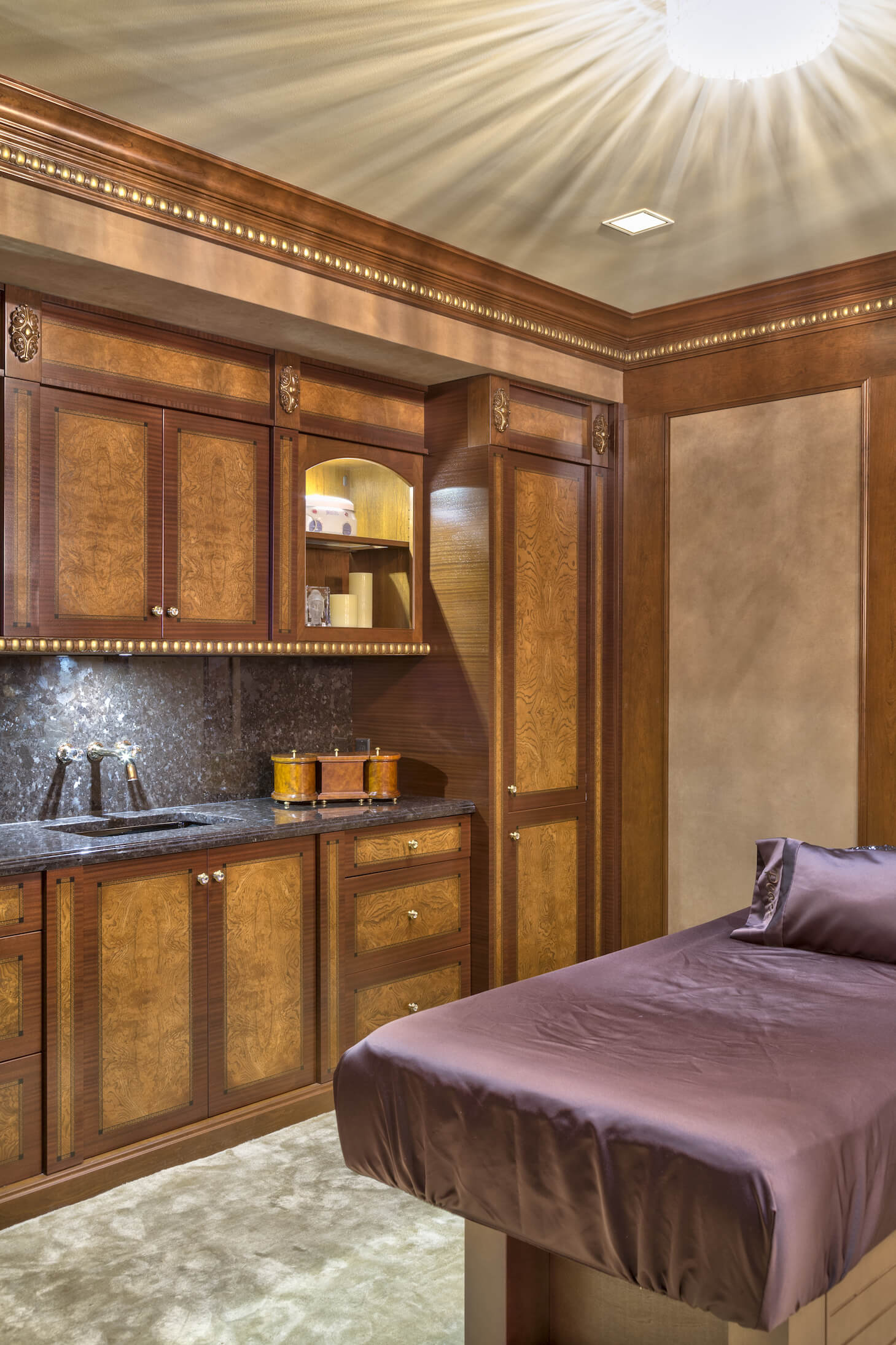 This retreat features a truly unique touch in the form of a massage room, replete with cushioned massage table and granite sink area, with storage for supplies in detailed wood cupboards.