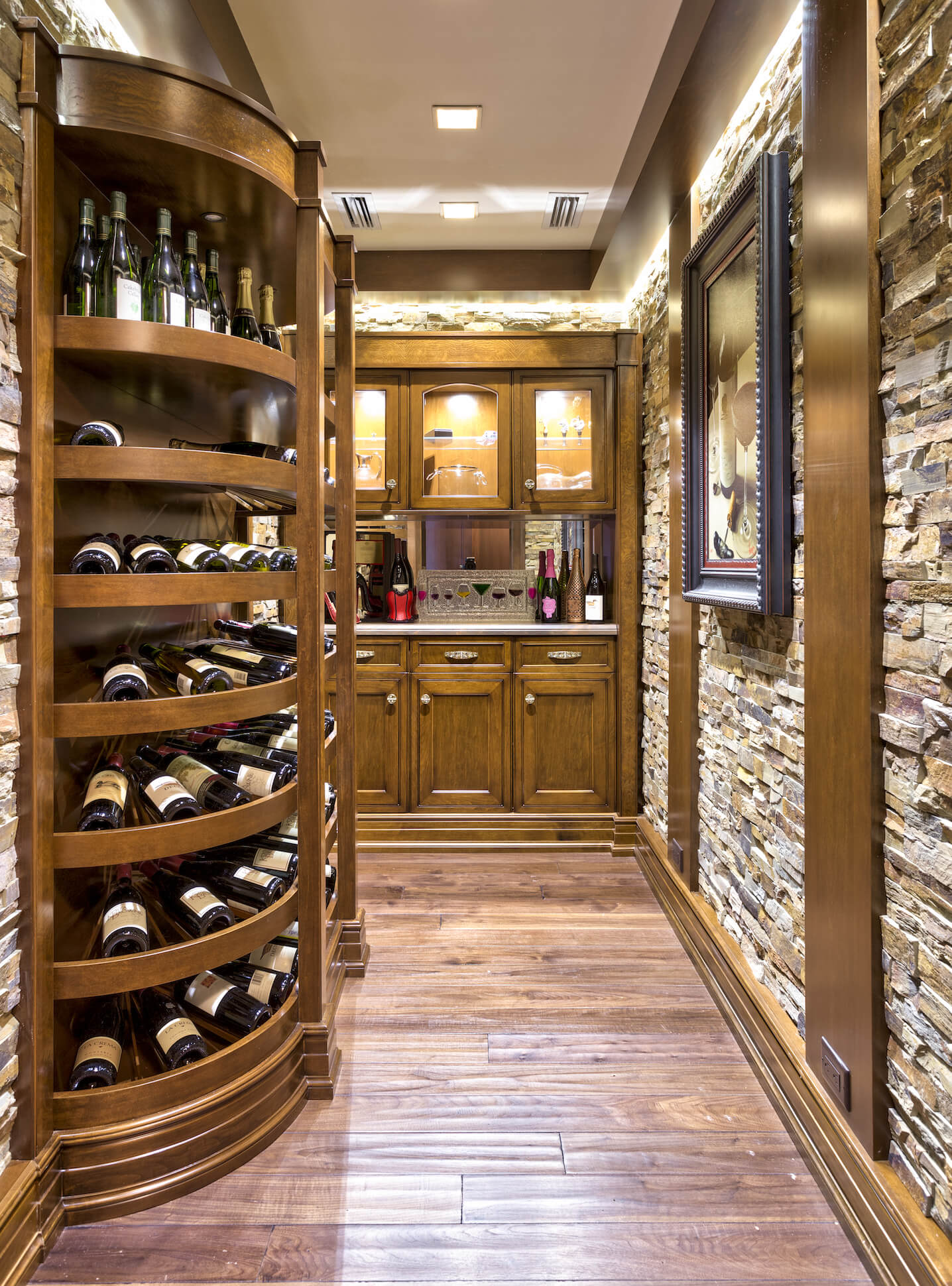 The luxurious wine cellar is decked out in a mixture of stone brick and rich timber, with curved racks at right, and small bar at center. Inner-lit cabinetry allows for bold display of glassware.