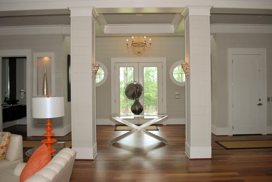 The subtle lines on the walls and columns add visual interest to the light taupe paint. The entryway opens directly into the main living room, with accents of orange. A small table, sconces on the inside of the columns, and the chandelier just above the doorway define the entry space.