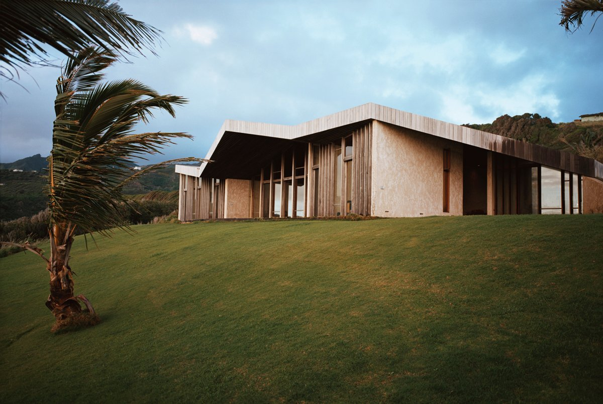 The ocean facing side of the home is a series of windows, unbroken except for slim vertical wood beams. The outline of the folded wooden sky deck roof are clearly appreciated from this angle.
