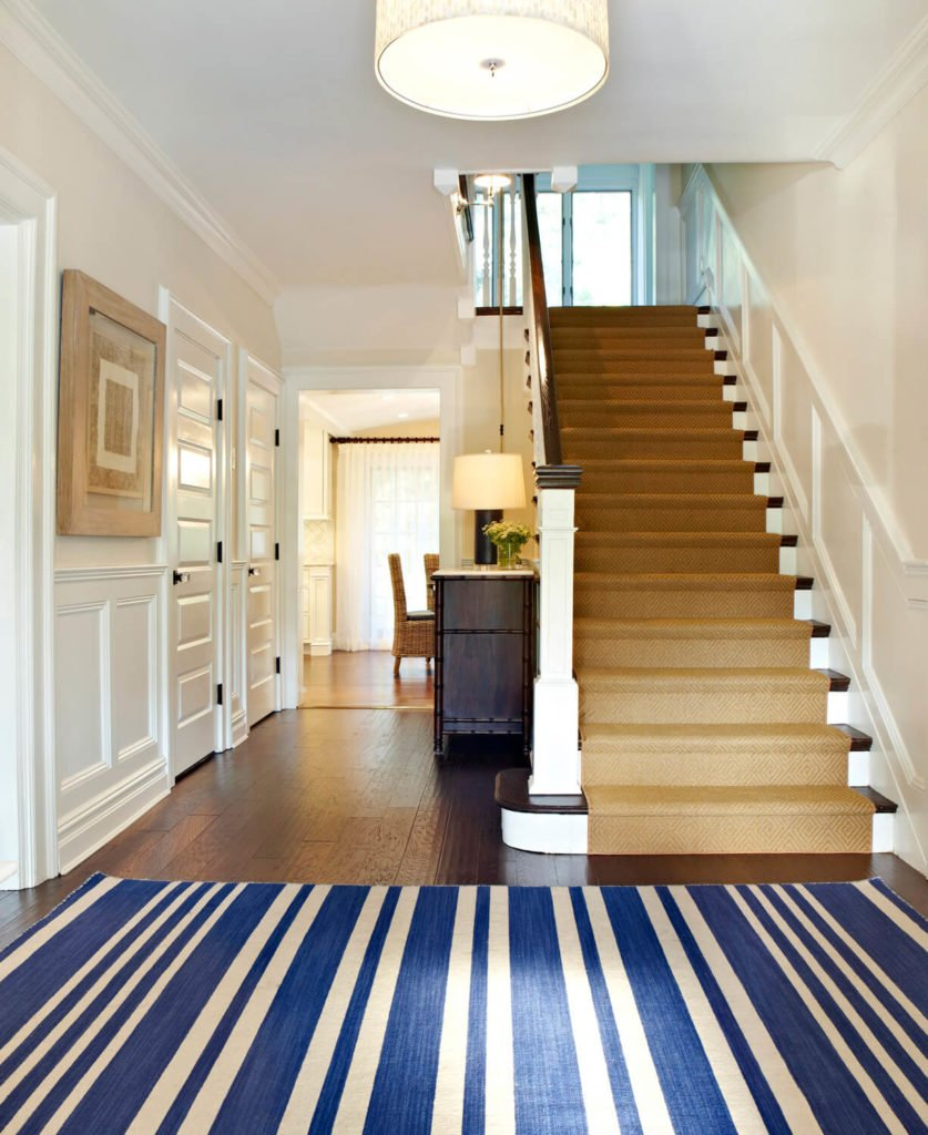 The rug upon entering the foyer is nautical in blue and cream. Stairs lead up to the second floor. Further down the hall is a dresser made of birch wood and bamboo, with a white marble top.