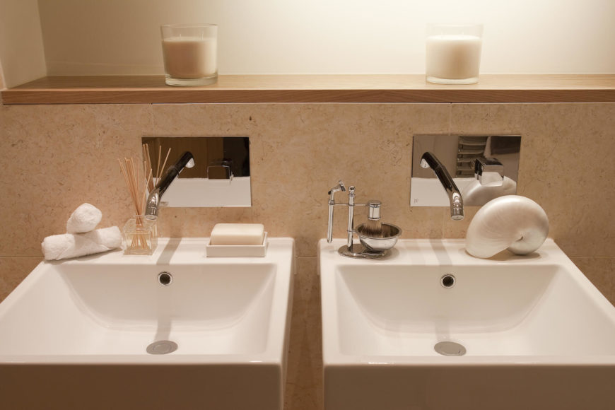 Bathroom features a pair of floating pedestal sinks as a vanity, with wall mounted faucets above.