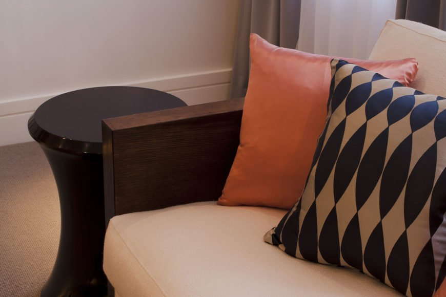 A close view of the sofa highlights the rich wood tones and contrast of patterned and colored pillows over the beige cushioning, which matches the carpet.