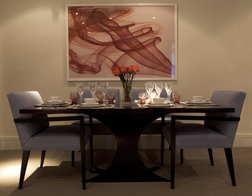 The dining area stands a luxurious black dining table surrounded by grey upholstered side chairs, with sensuous, red painting overhead. This mixture exemplifies the overall aesthetic of the home.