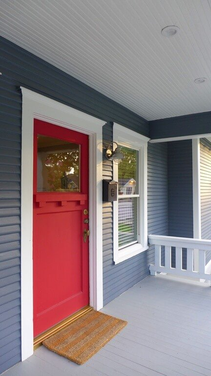 The blue siding of this home contrasts beautifully with the red door. The small white railings on either side of the raised porch match the pristine white trim around the door and window.