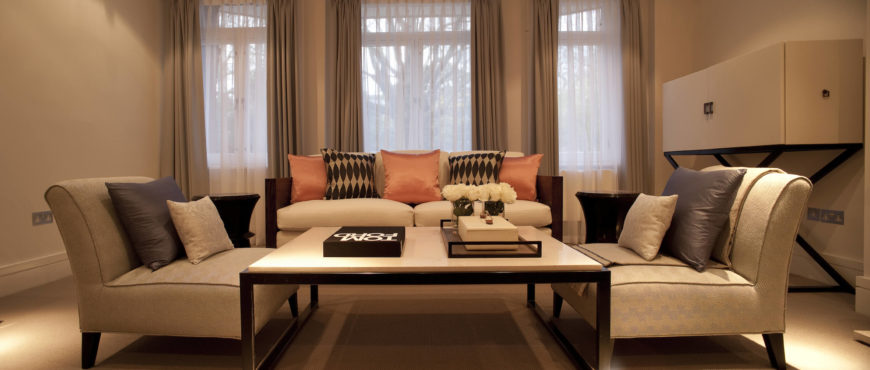 Living room with tan walls, curtains and furniture by Roselind Wilson Design