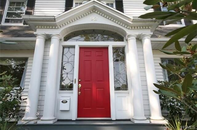 This door is a typical cottage-style front door. The red front door has rectangular panels with a golden colored handle and locks. The sidelights on both sides have clear glass panels with geometric designs. The transom is also made of clear glass and is attached to white framing. The red and white cottage-style door has four pillars and a mailbox affixed at the left side just below the sidelight.