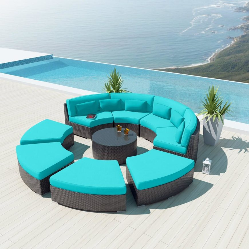 This bold patio sectional sets bright blue cushioning over black rattan construction, placing an entire circle of seating around a central coffee table piece. One half has full back design, while the other half can be segmented into individual ottoman-like chairs.