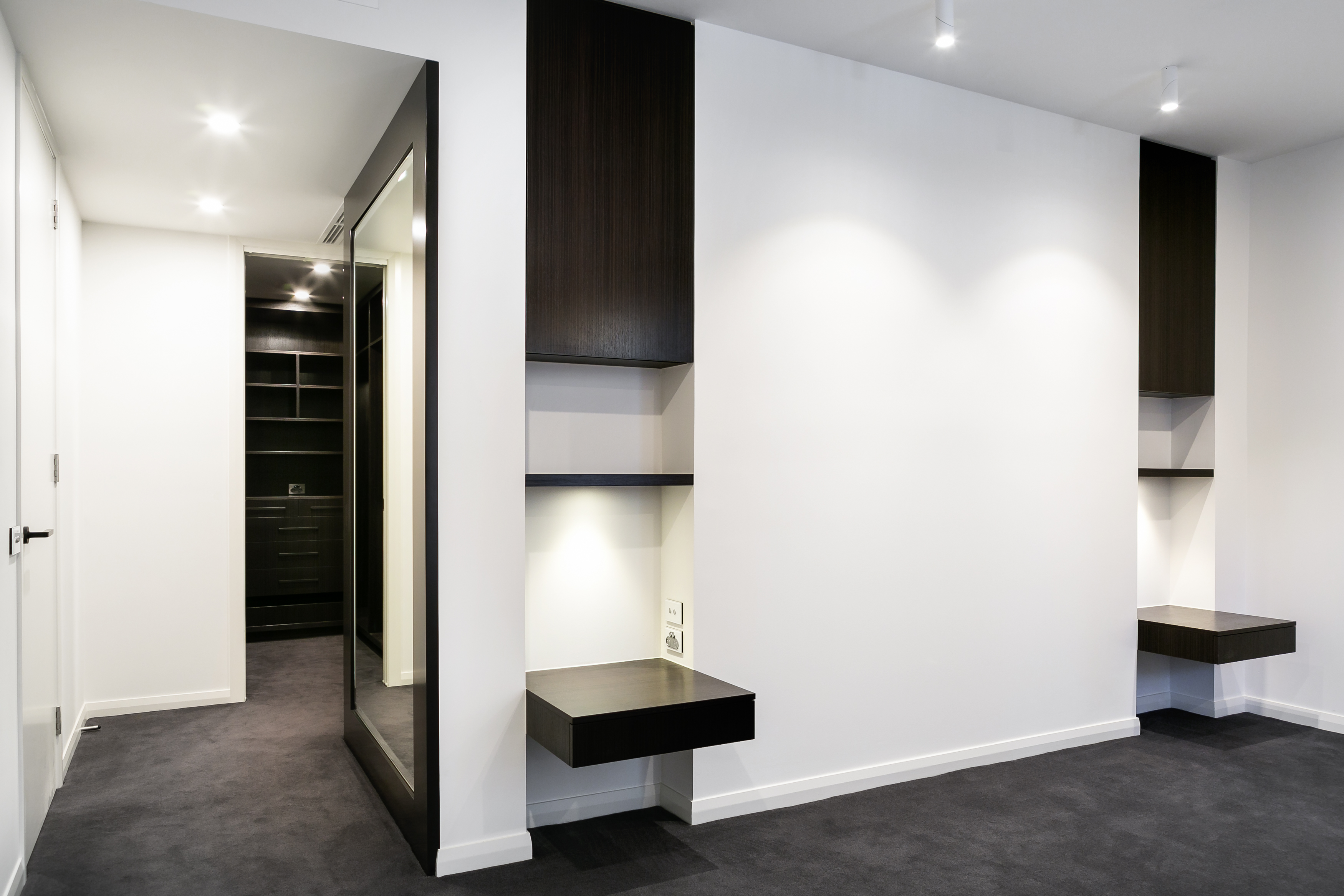 The primary bedroom en suite holds this unique wall detail, with built-in dark wood shelving on white walls, designed to flank the bed. To the left, we see an opening toward the grand walk-in closet.